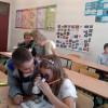 Uczniowie szkoły podstawowej uczą się obsługi mikroskopu.